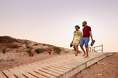 Shot of young african couple walking on the wooden footwalk over the dunes near the beach