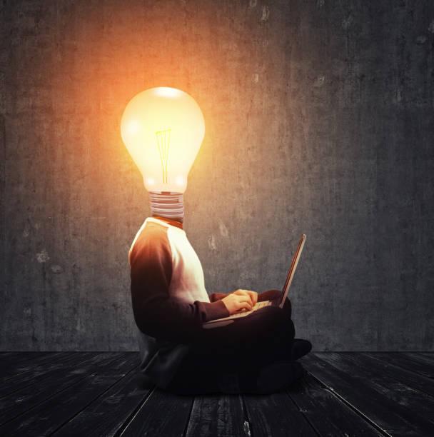 無頭的人, 有一個點燃的燈泡, 而不是頭在筆記本電腦上工作。 - 被砍頭 個照片及圖片檔