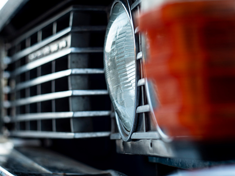 Headlight and grille closeup of an old beautiful car. copy space Concept for bumper repair, car sale. retro cars