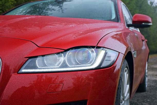 Headlight in a modern car Berlin, Germany - 13 October, 2015: View on the headlight with LED in a modern car on the road. The LED lights has become the norm in a modern cars. jaguar xj stock pictures, royalty-free photos & images