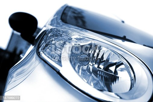 Close up of the head lights of a new car. The color of the car is silver metallic, blue. The background is white. Front view, left wing. photographed with a 50mm prime lens and full frame camera.modern car-light, isolated on white, toned image
