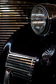 The headlight of an antique, rarity, vintage black car.
