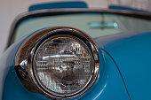 The headlight of an old, rarity, vintage blue car.