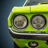 Isolated image of the headlights of a bright green American sports car