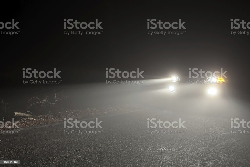 Headlights of a car driving in the fog at night stock photo