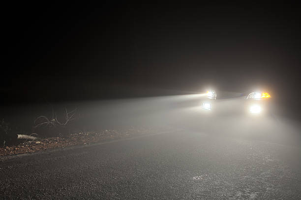 headlights of a car driving in the fog at night - mist donker auto stockfoto's en -beelden