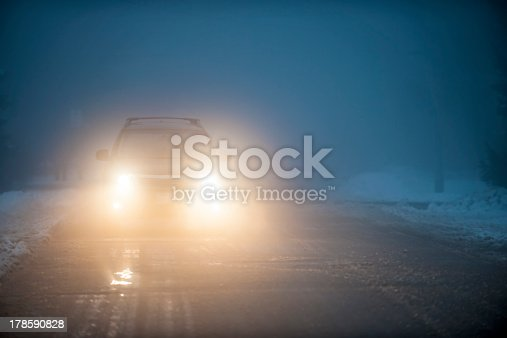 Bright headlights of a car driving on foggy winter road