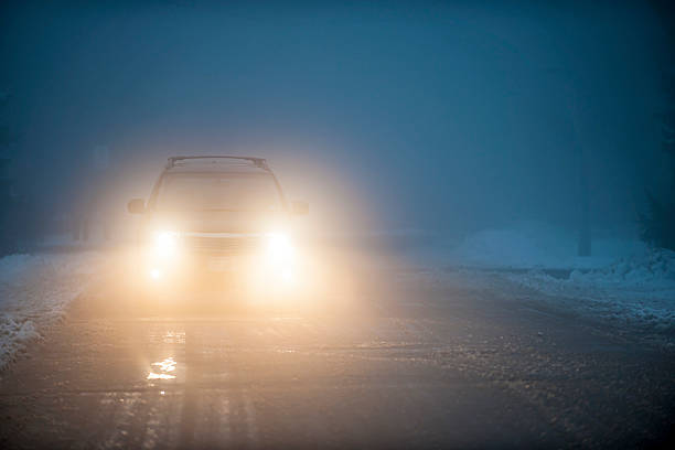 headlights of car driving in fog - mist donker auto stockfoto's en -beelden