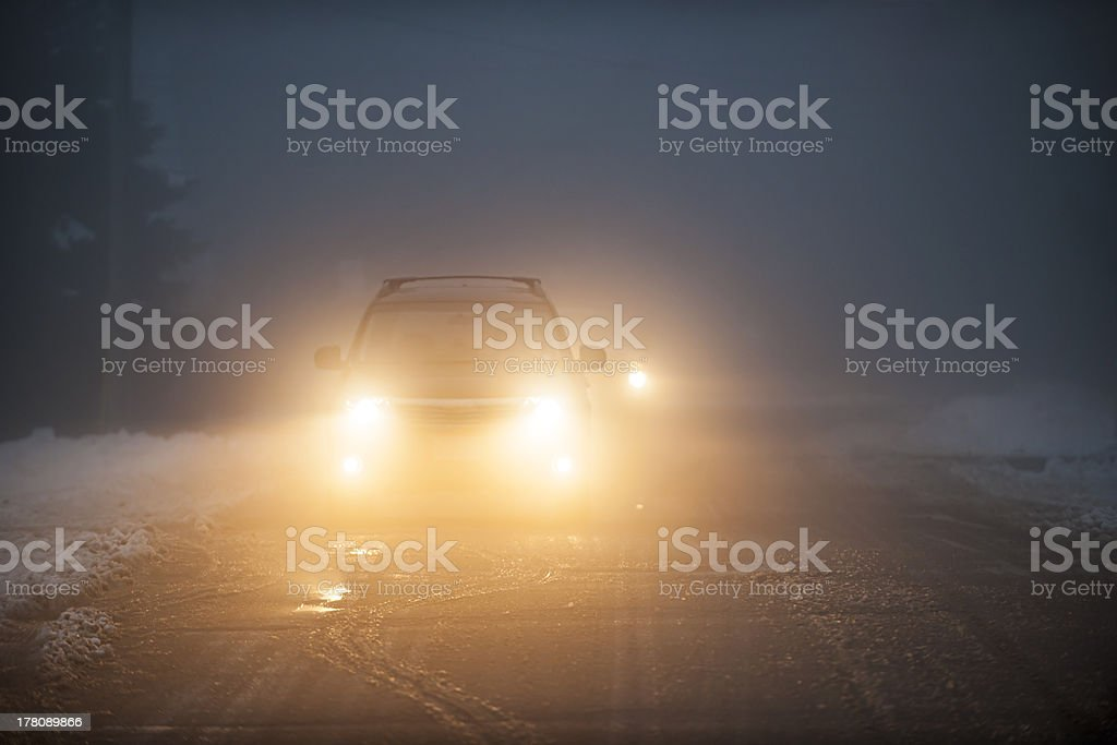 Headlights of cars driving in fog at night stock photo