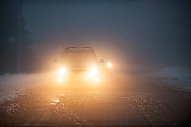 headlights of cars driving in fog at night - mist donker auto stockfoto's en -beelden