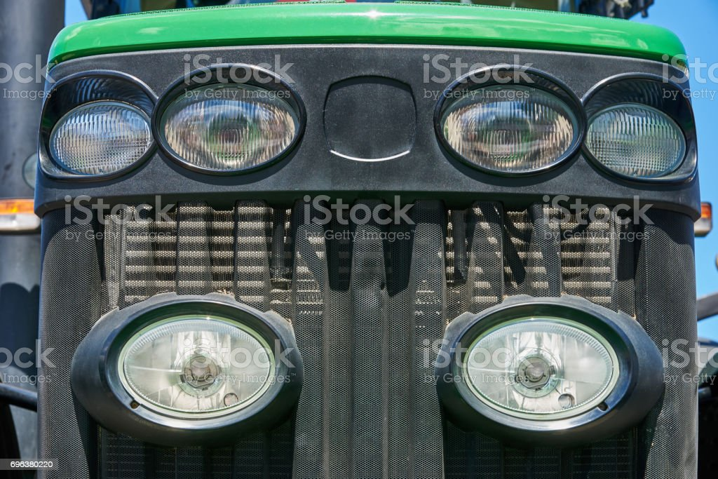 Headlights on the radiator grille of the tractor stock photo