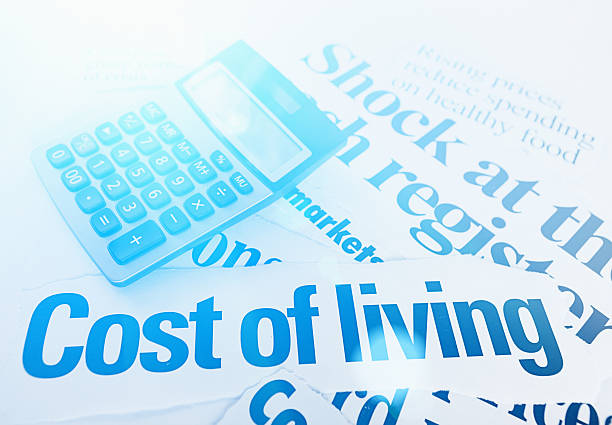 Headlines on cost of living with calculator. Blue toned. stock photo
