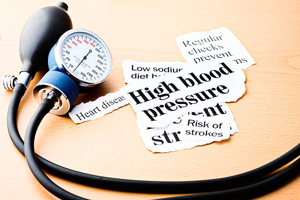 Headlines on hypertension with blood pressure meter Headlines on high blood pressure, heart disease, and the risk of strokes on a wooden desk next to a blood-pressure gauge. hypertensive stock pictures, royalty-free photos & images