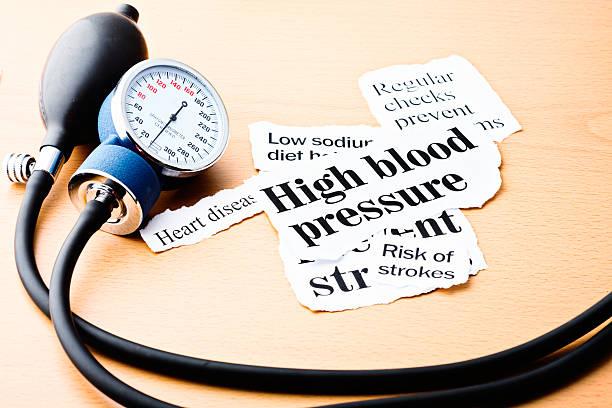 Headlines on hypertension with blood pressure meter stock photo
