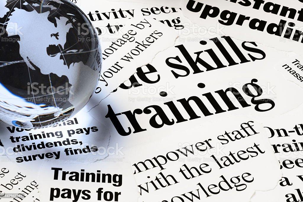 Headlines on staff empowerment through training under globe paperweight royalty-free stock photo