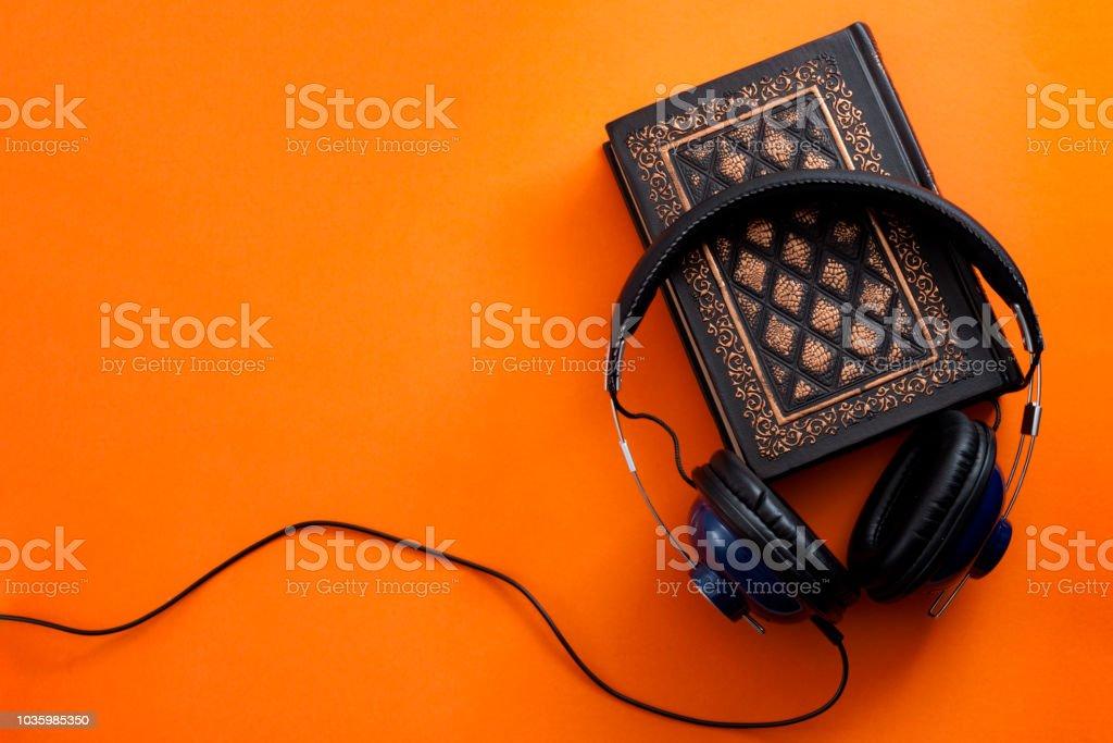 Fones de ouvido e um livro vintage contra um fundo laranja - foto de acervo