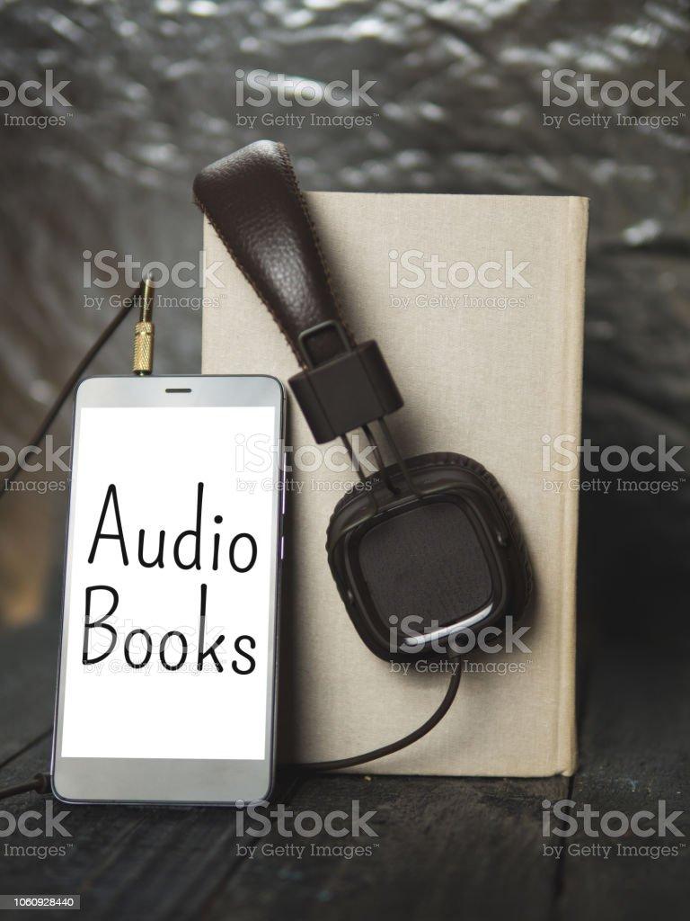 fones de ouvido e livro sobre fundo escuro de madeira. Conceito de audiobook - foto de acervo