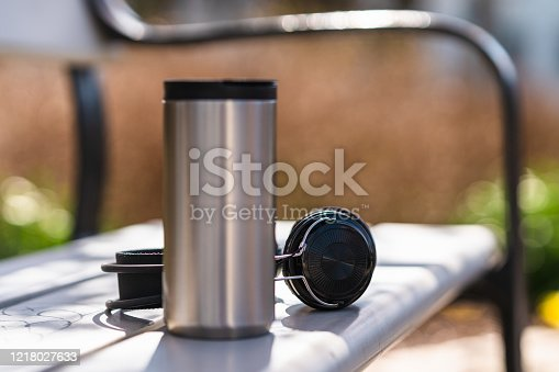 A reusable travel mug in stainless steel next to some headphones on a park bench. Focus on the headphones.
