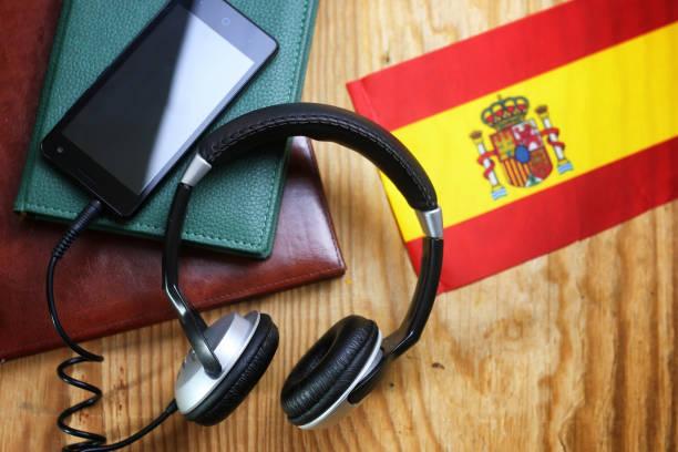 headphones and flag on a wooden background - spanisch translator stock-fotos und bilder