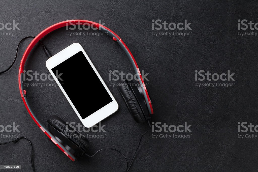 Headphones and smartphone on desk stock photo