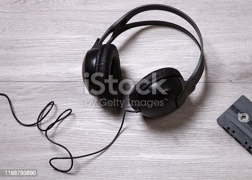 Headphones and vintage cassette on wooden floor