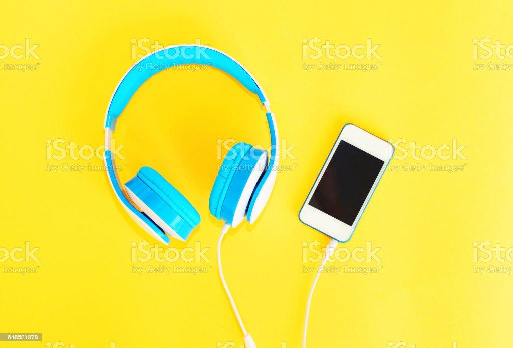 Auriculares conectados al smartphone blanco sobre un fondo amarillo - foto de stock