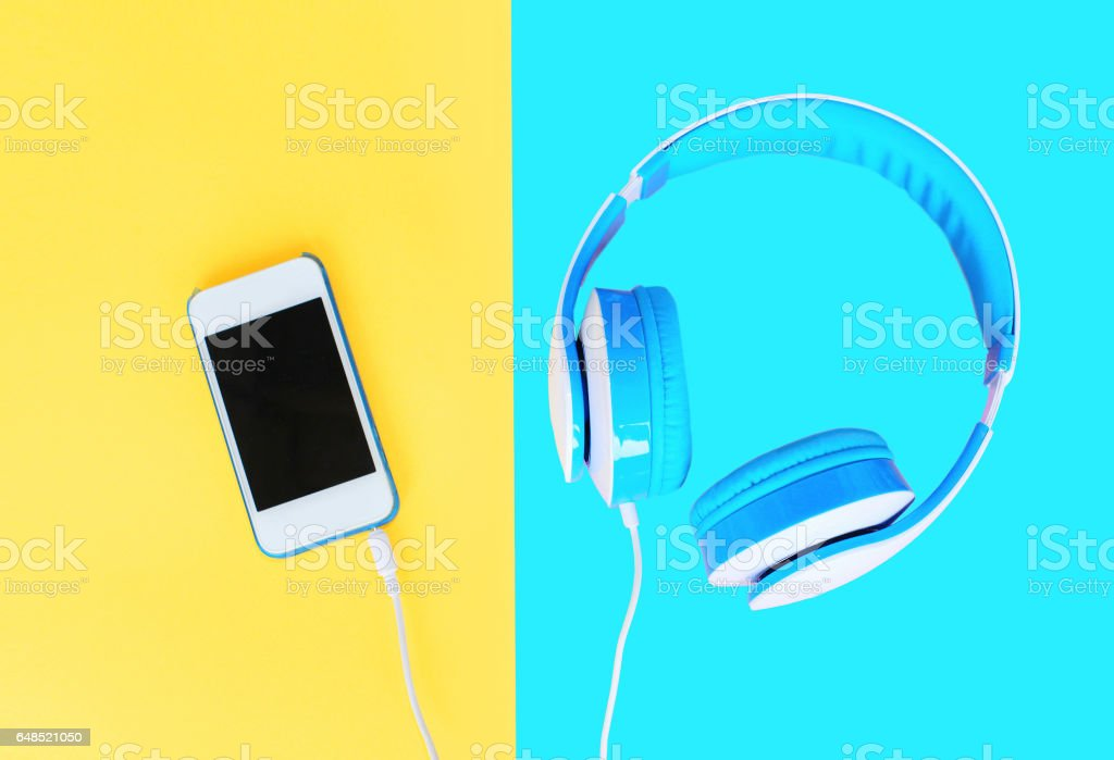 Headphones connected to white smartphone over colorful yellow blue background stock photo