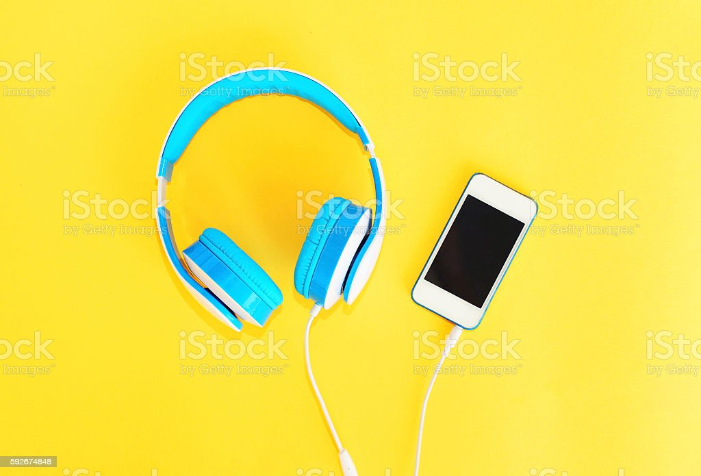 Headphones connected to white smartphone over yellow background stock photo