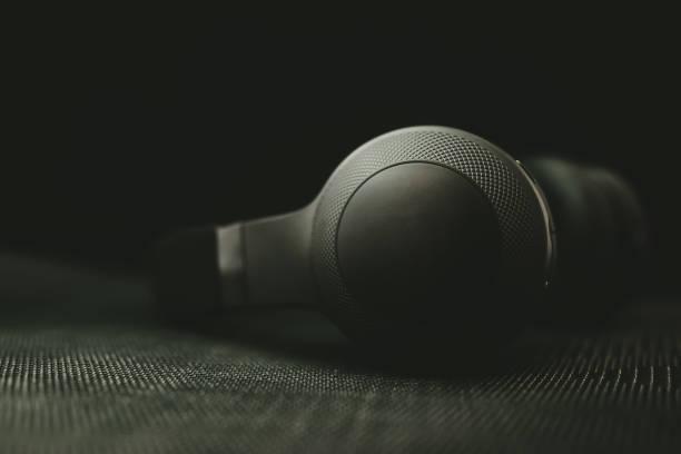 auriculares en la oscuridad - auriculares equipo de música fotografías e imágenes de stock