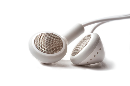 Close up photo of white headphones on a white background.