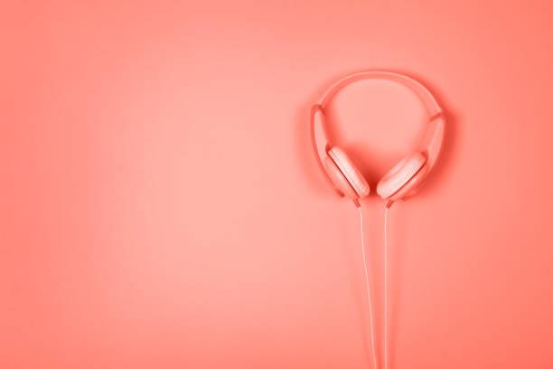 Blaue und gelbe Kopfhörer auf rosa Hintergrund mit Textfreiraum. – Foto