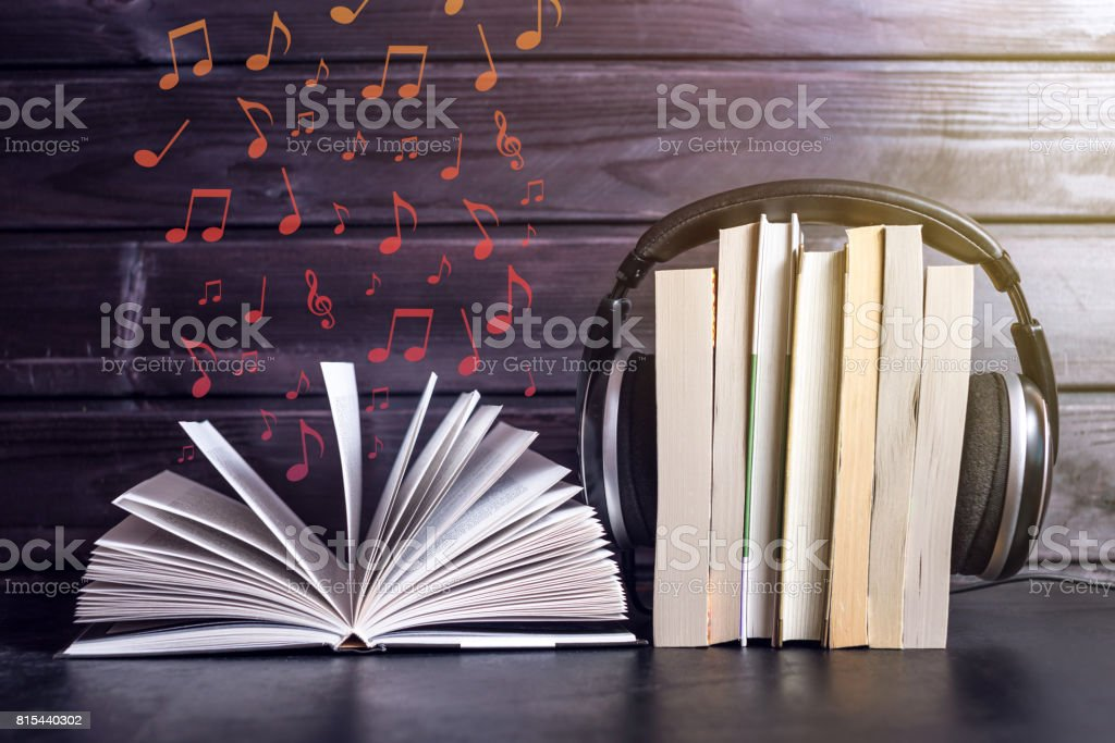 Headphones on books and flying notes. The concept of audiobooks stock photo