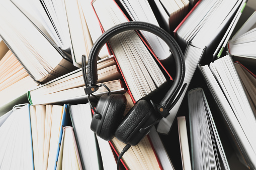 Headphones on many books background, top view