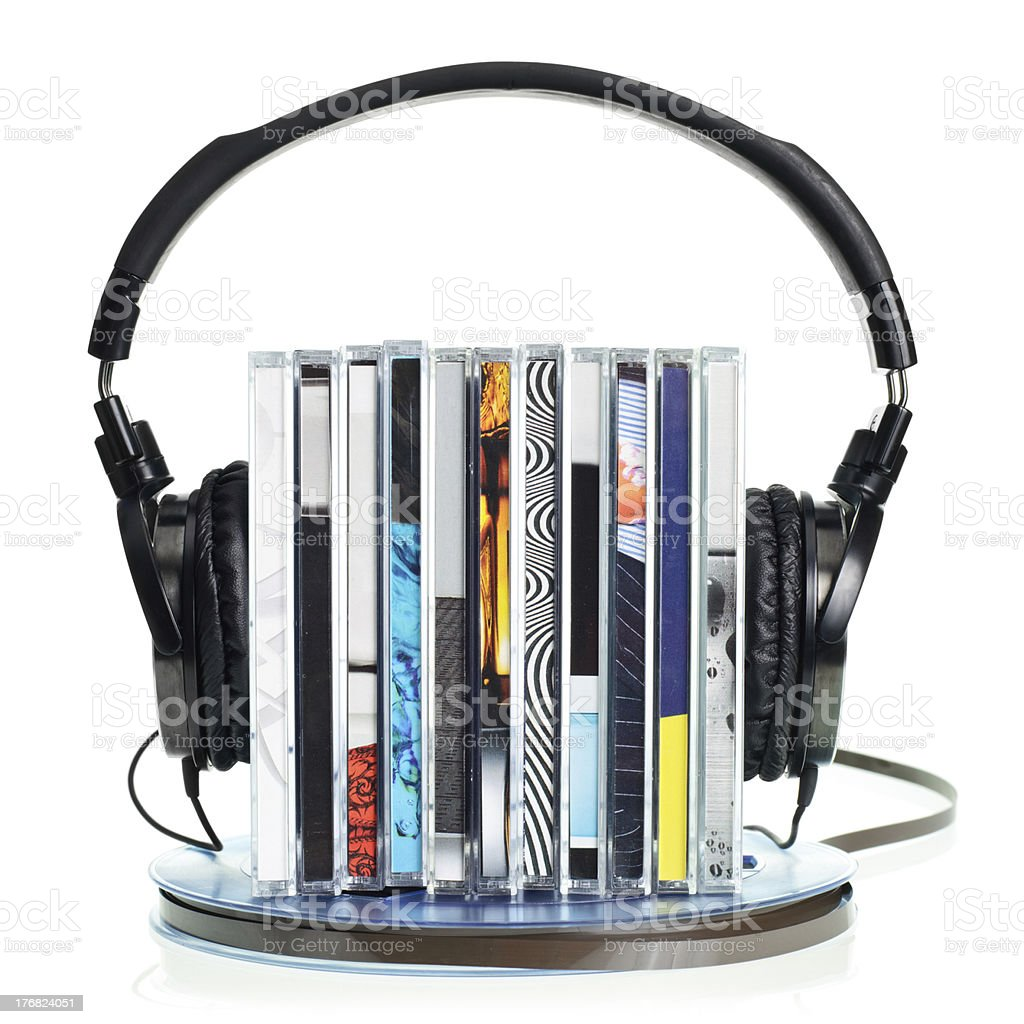 Headphones on stack of CDs and a reel tape stock photo