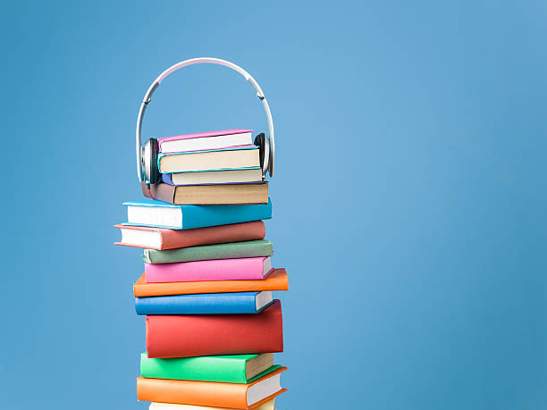 Headphones On Top Of Multicolored Hardcover Books For Audio Reading stock photo