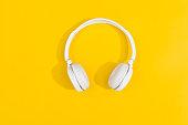 White wireless headphones on yellow background