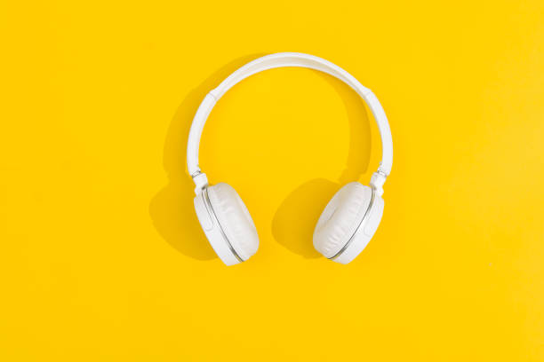 Headphones White wireless headphones on yellow background headphones stock pictures, royalty-free photos & images