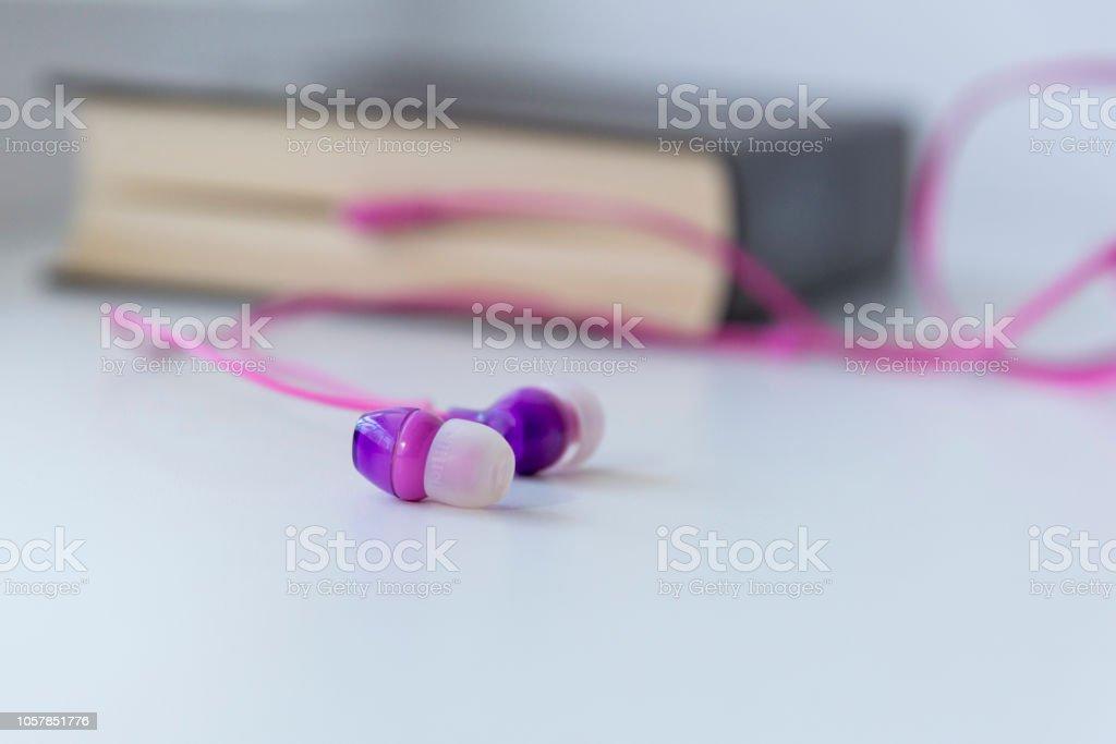 Fones de ouvido, saindo de um livro sobre um fundo claro, o tema de um audiolivro - foto de acervo