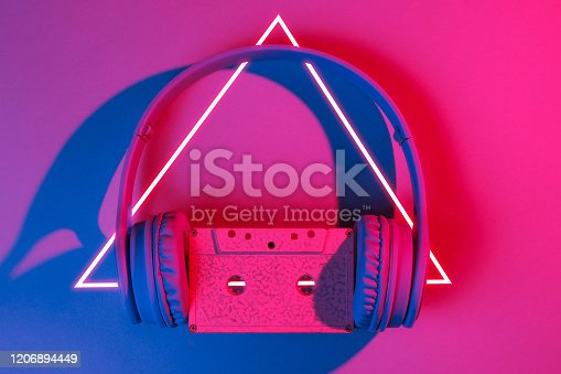 istock Headphones with audio cassette. 80's synth wave and retrowave glowing triangle futuristic aesthetics. Old fashioned abstraction concept 1206894449
