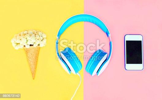 istock Headphones with ice cream cone flowers white smartphone over colorful 592673142