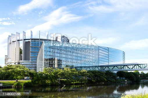 Modern Headquarter of European Parliament in Strasbourg with calm flowing Ill river and passerelle to the old building