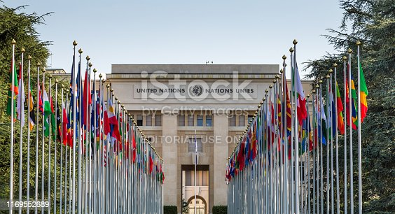 Geneva, Switzerland - 6 August, 2019: color image depicting the exterior architecture of the United Nations (UN) building in the city of Geneva, Switzerland. The front of the building is lined with many flags and flagpoles, representing all the member nations of the UN. Room for copy space.