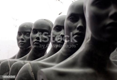 Abandoned mannequins standing in front of a dirty window in warehouse