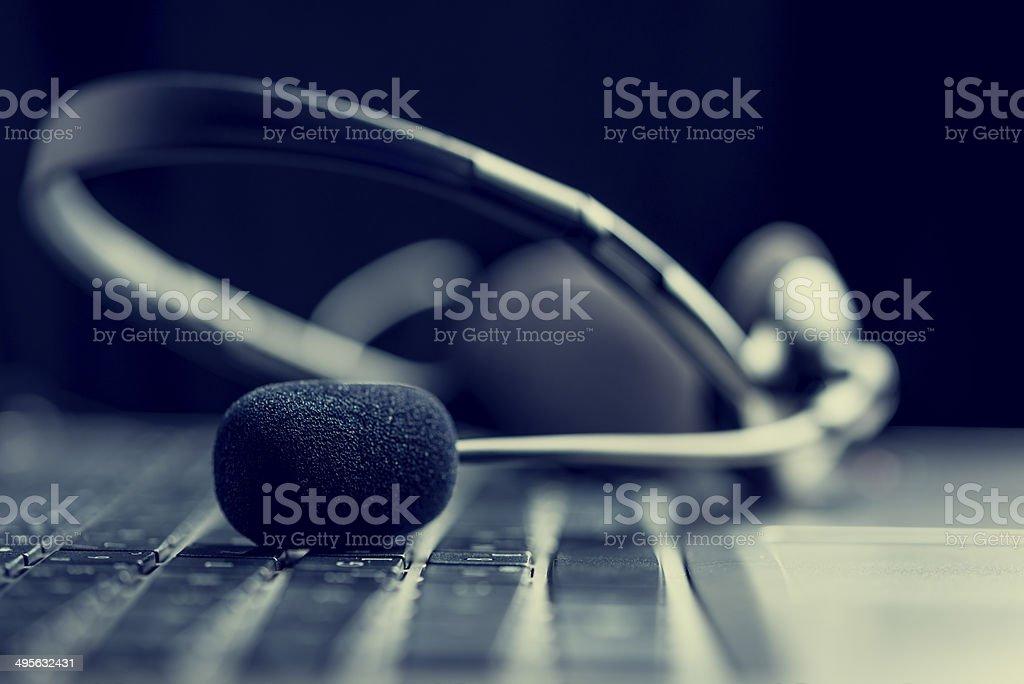 Headset lying on a computer keyboard stock photo