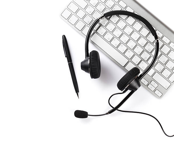 Headset, pen and keyboard Headset, pen and keyboard. Call center support. Isolated on white background hands free device stock pictures, royalty-free photos & images