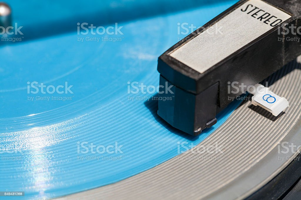 headshell of old turntable on blue flexi disc stock photo