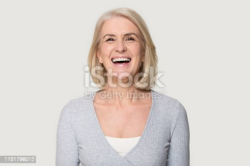 istock Headshot happy aged female laughing posing on grey studio background 1151796012