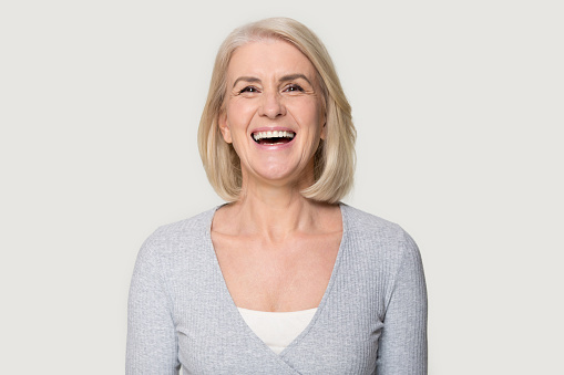 Head shot portrait overjoyed blond middle aged female smiling look at camera laughing feels happy pose isolated on grey studio background, advertise clinic procedure dental care prosthesis for seniors