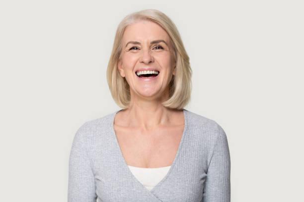 headshot glücklich gealtertes weibchen posiert auf grauem studio-hintergrund - zahnimplantat stock-fotos und bilder