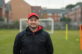 Headshot of a male football coach standing on the soccer field while looking at the camera and smiling.